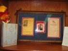Koa framed Historical items:  Cornerstone Day program,  Washington Place commemorative ornament with Queen Lili`uokalani portrait,  Flag Raising Day program